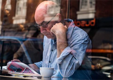 Older man reading in cafe